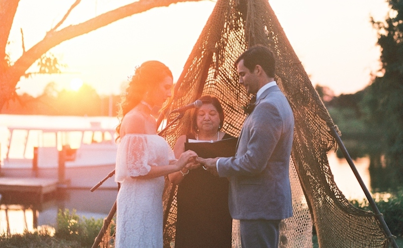 Wedding couple and officiant at sunset