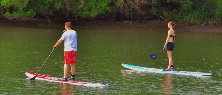 Stand up paddleboarding guests on creek
