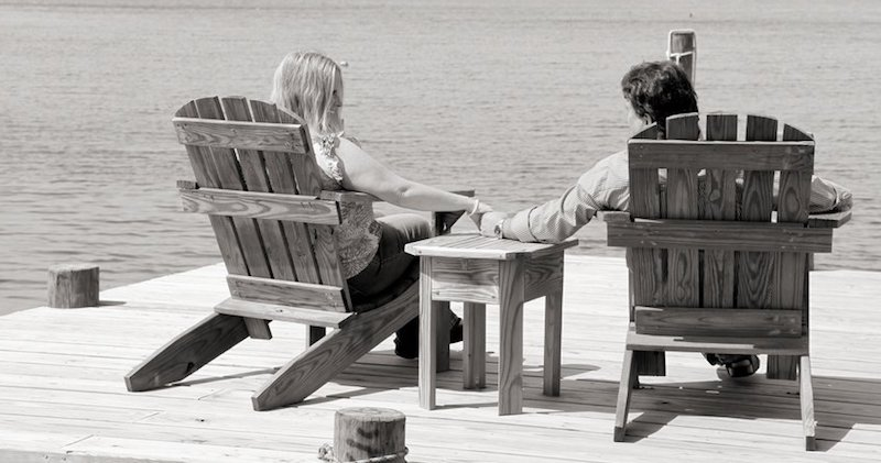 engagement couple holding hands on dock
