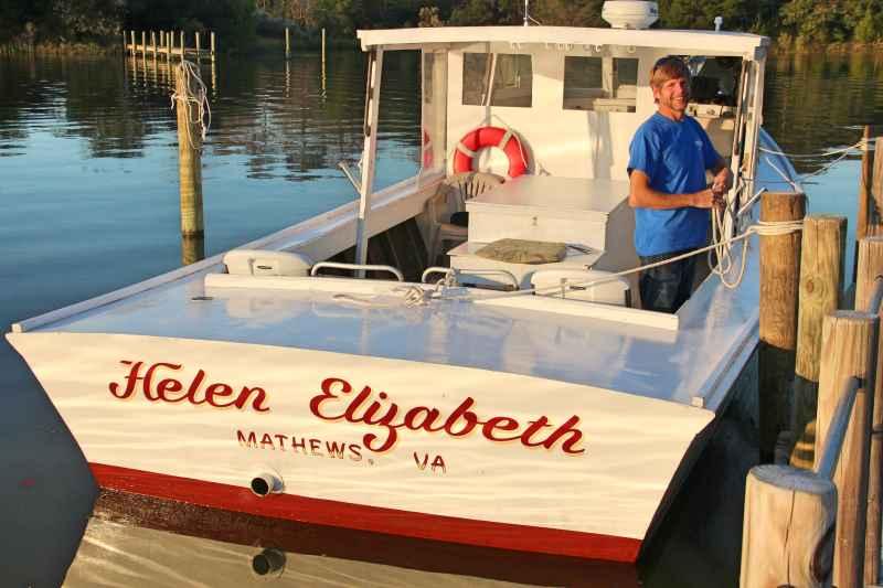 Captain Trey standing on his Chesapeake Deadrise Boat