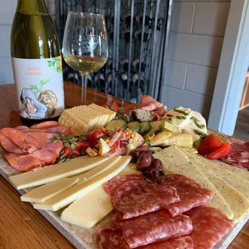 Bottle and glass of Zoll wine with a charcuterie board
