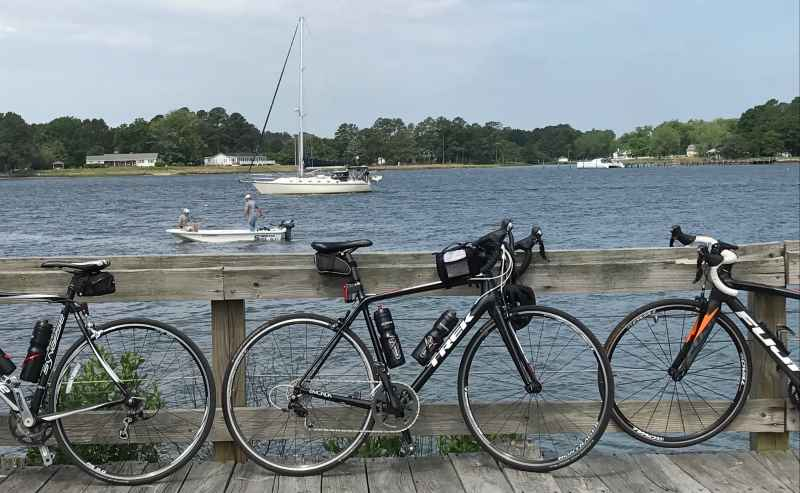 3 bike on a dock with water and boats in the background