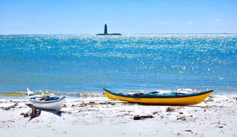 2 kayaks on the beach with a lighthouse in the far distance