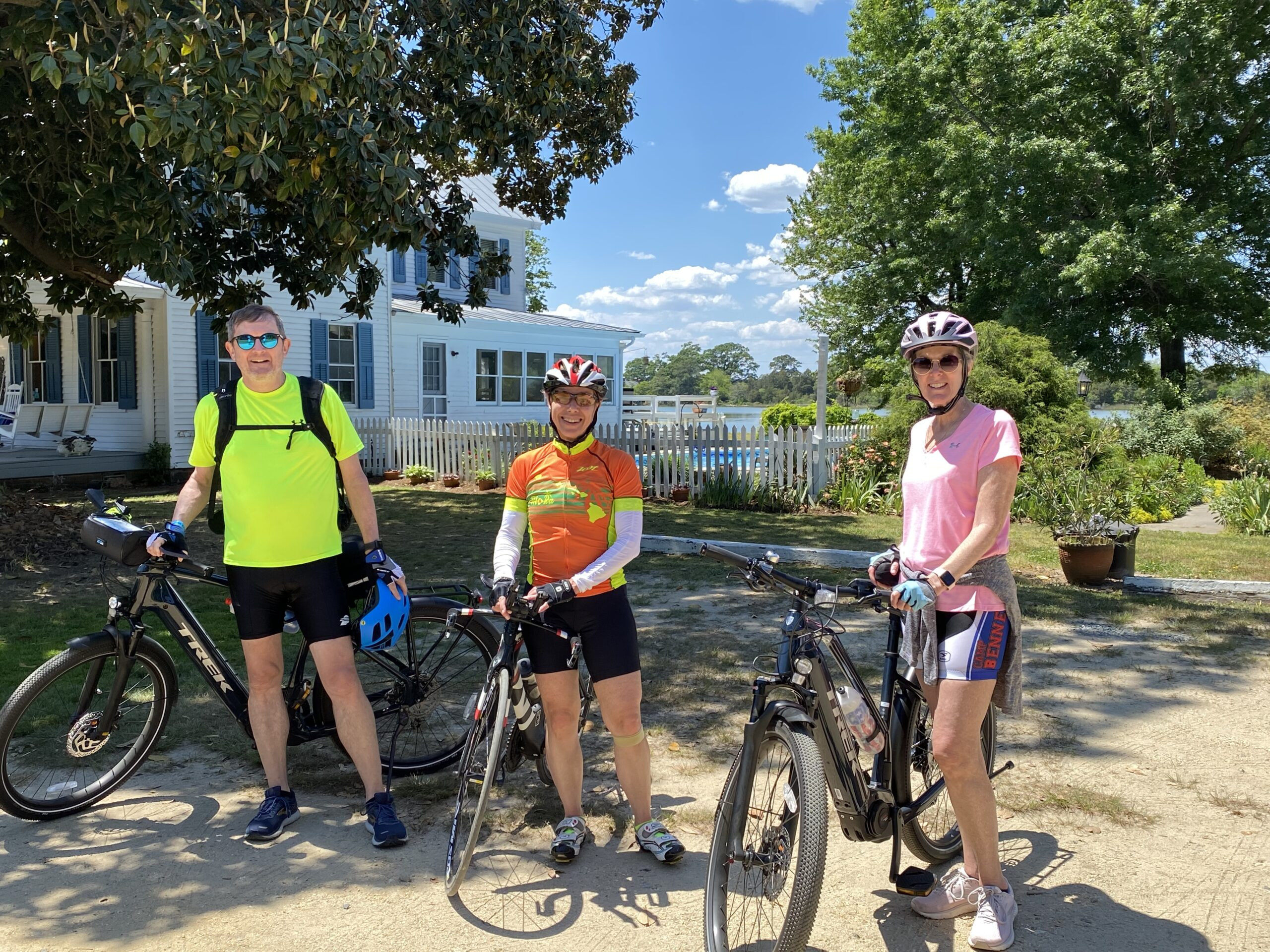 3 cyclist standing outside of Inn with bikes