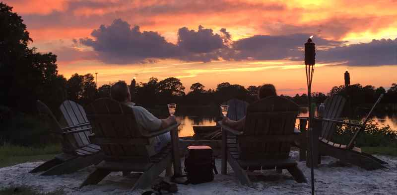 romantic picture of a couple sitting at firepit at sunset